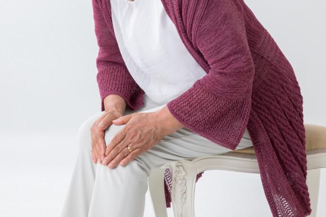 膝を抱える高齢者の写真